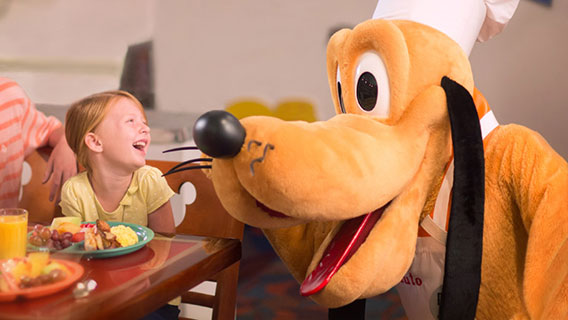 Mother and daughter enjoying a meal with Pluto at Chef Mickey's