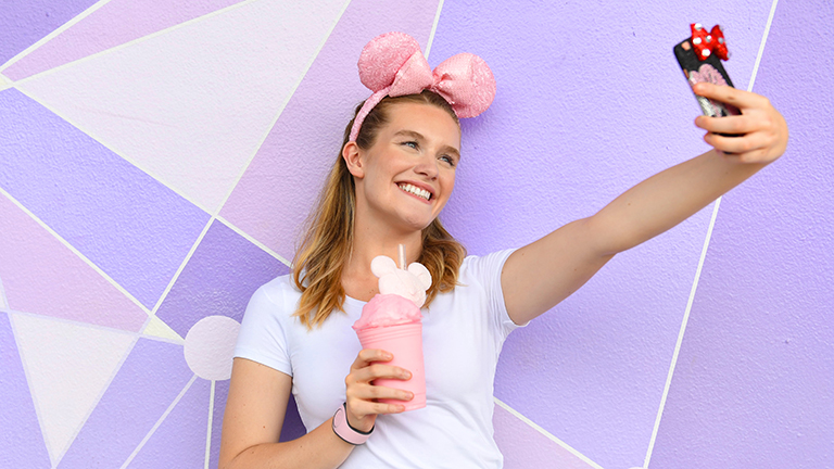Teen posing in front of the purple wall in Magic Kingdom