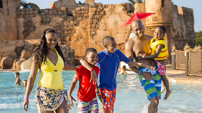 Family going for a dip in the pool at Disney's Caribbean Beach Resort