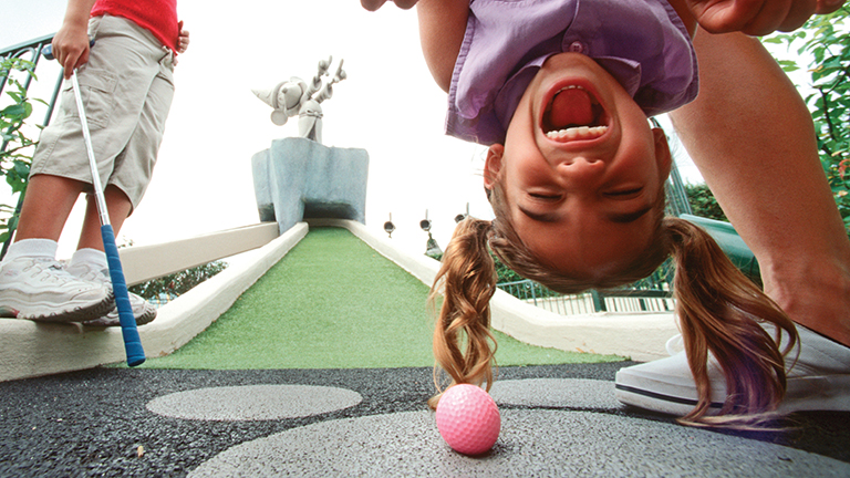 Young guest enjoying a round of mini-golf at Fantasia Gardens